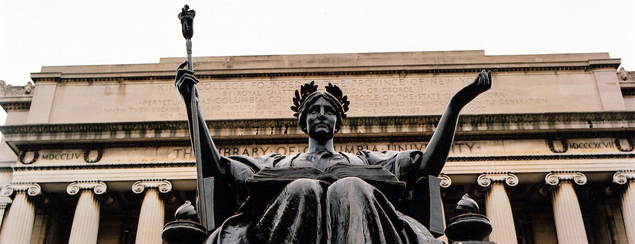 An image of a statue of a seated woman holding a mace in her right hand with a neo-classical columned building in the background