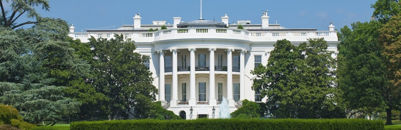An image of a large white house with columns and trees around it