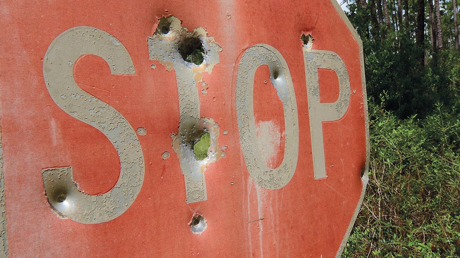 A stop sign with bullet holes