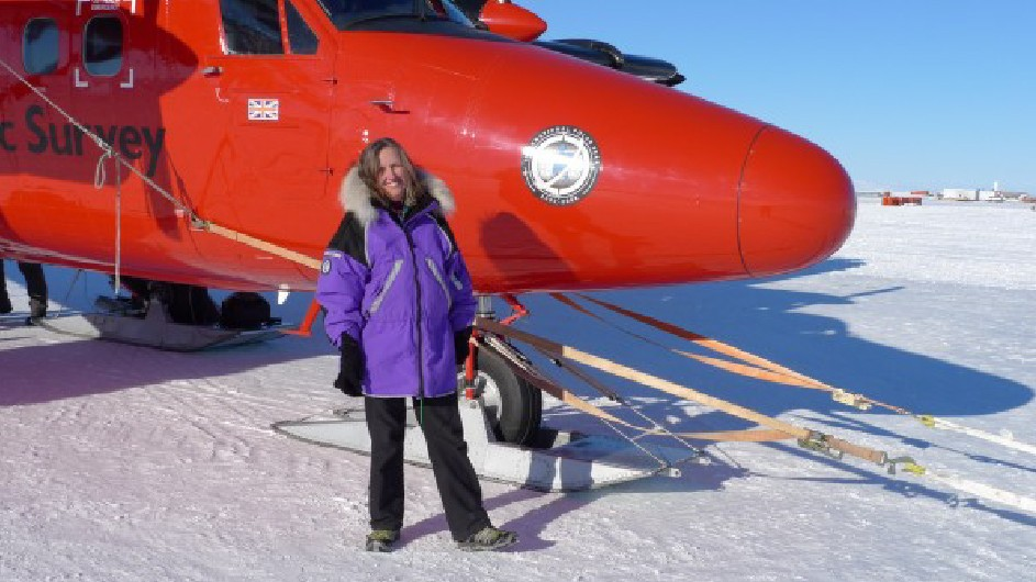 A photo of a woman in a purple parka standing next to a red plane on ice and snow.