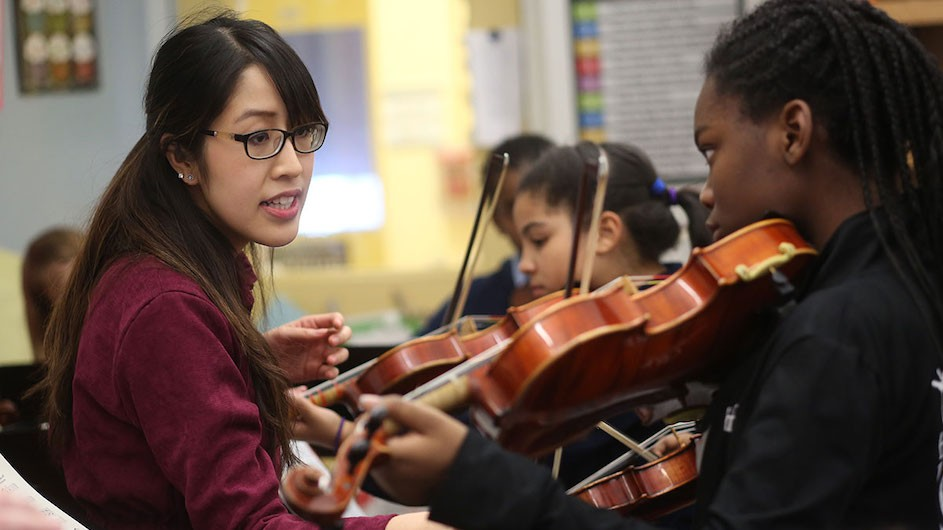 An image of a woman with long dark hair and glasses teaching a student to play the violin